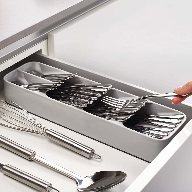 A utensil organiser holding different stainless steel utensils.