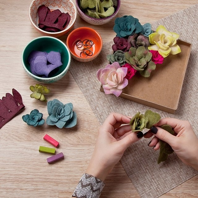 A model making a felt succulent next to some premade ones