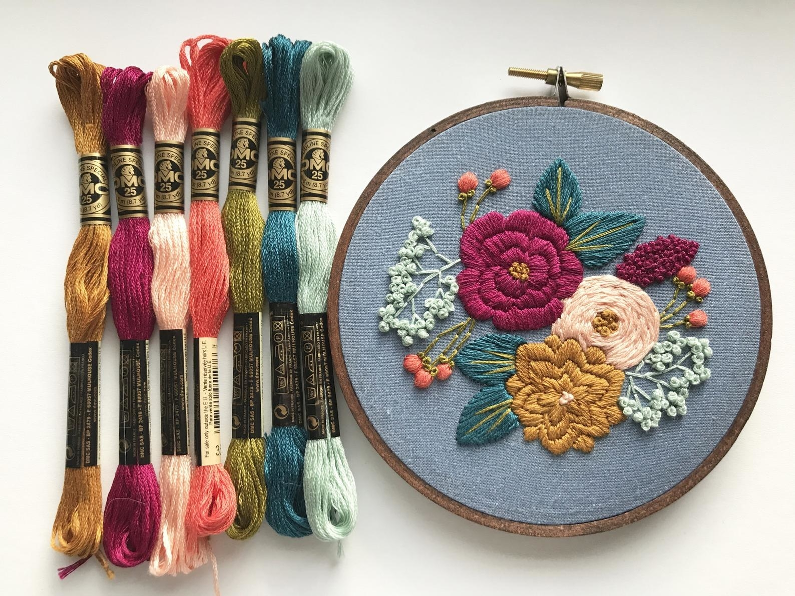 The embroidery shows three colorful flowers