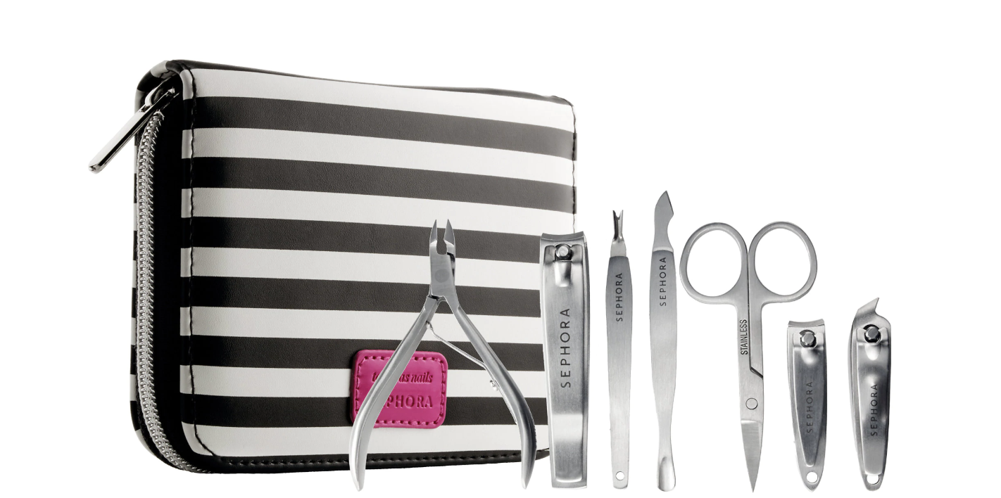 Silver nail files, cuticle trimmers, scissors, and more manicure equipment next to black-and-white zip case
