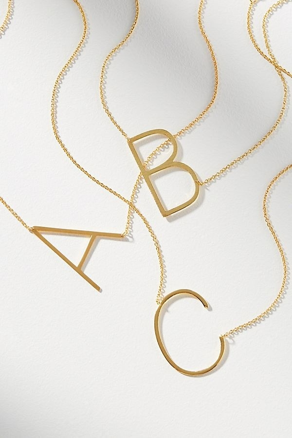 three gold necklaces with oversized initials on them