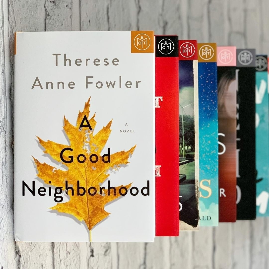 """A Good Neighborhood"" stacked on top of other books"