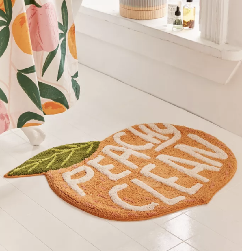 "a peach shaped bath rug that says ""peachy clean"""