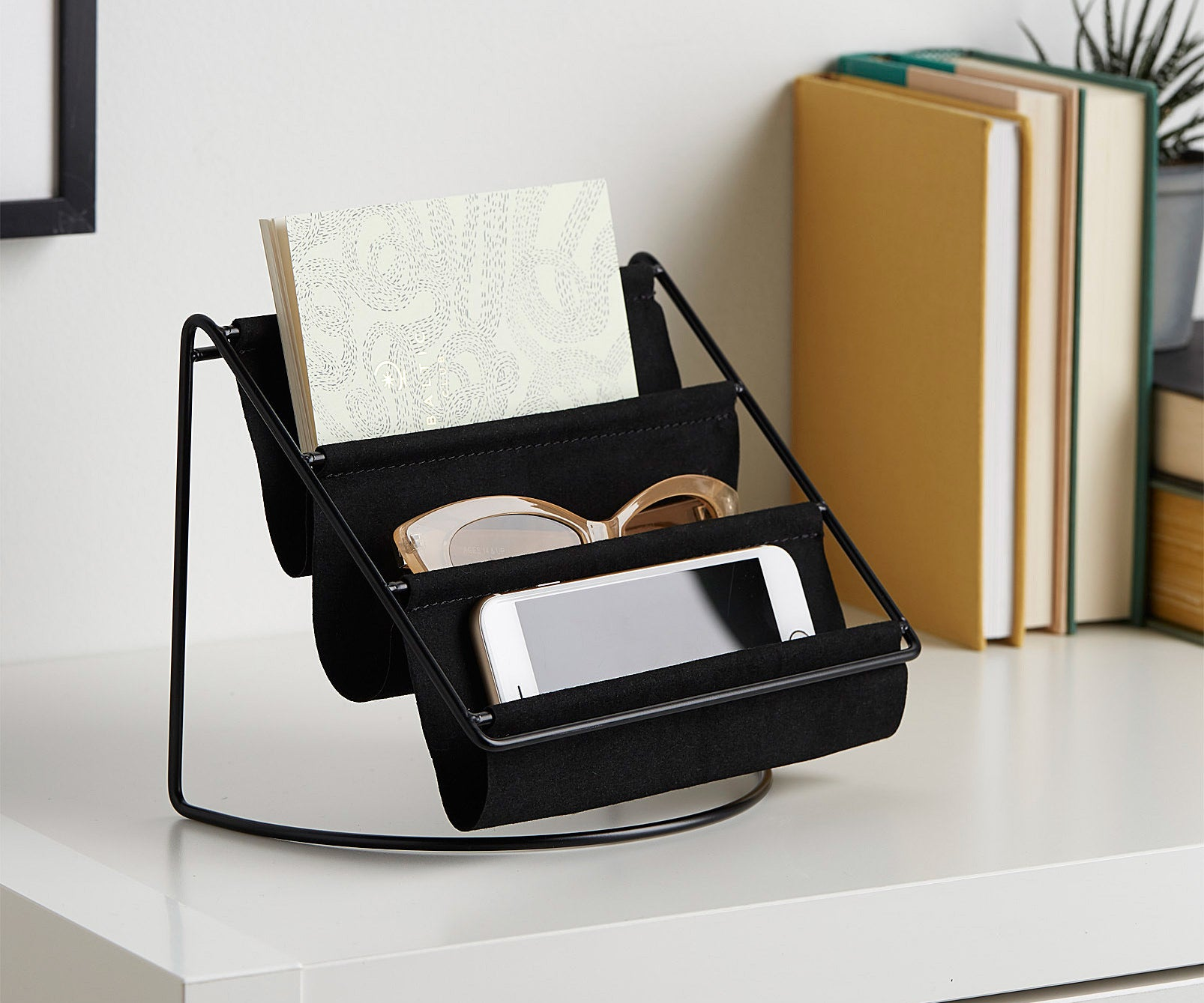 A three-tiered rack with a metal frame and cloth shelves There is a phone in one, a pair of sunglasses in another, and a small notepad in the top one.