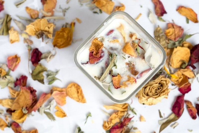 A flat lay shot of the candle in a cube glass container surrounded by flower petals