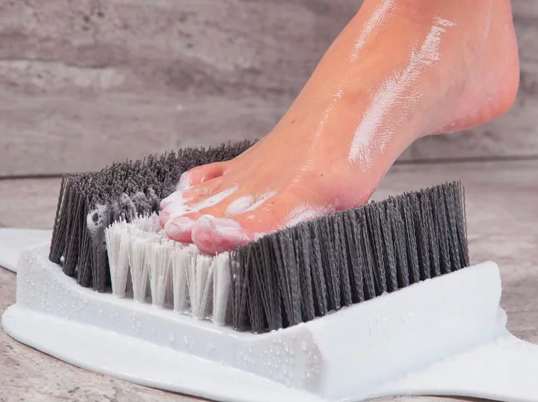 person washing and massaging foot on a massager stuck on the shower floor with high bristles