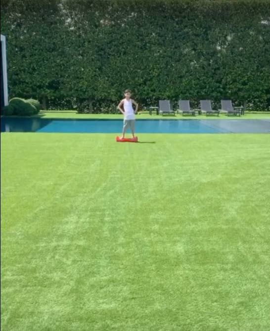 J Lo's son standing on a hoverboard in front of their swimming pool in her large manicured backyard
