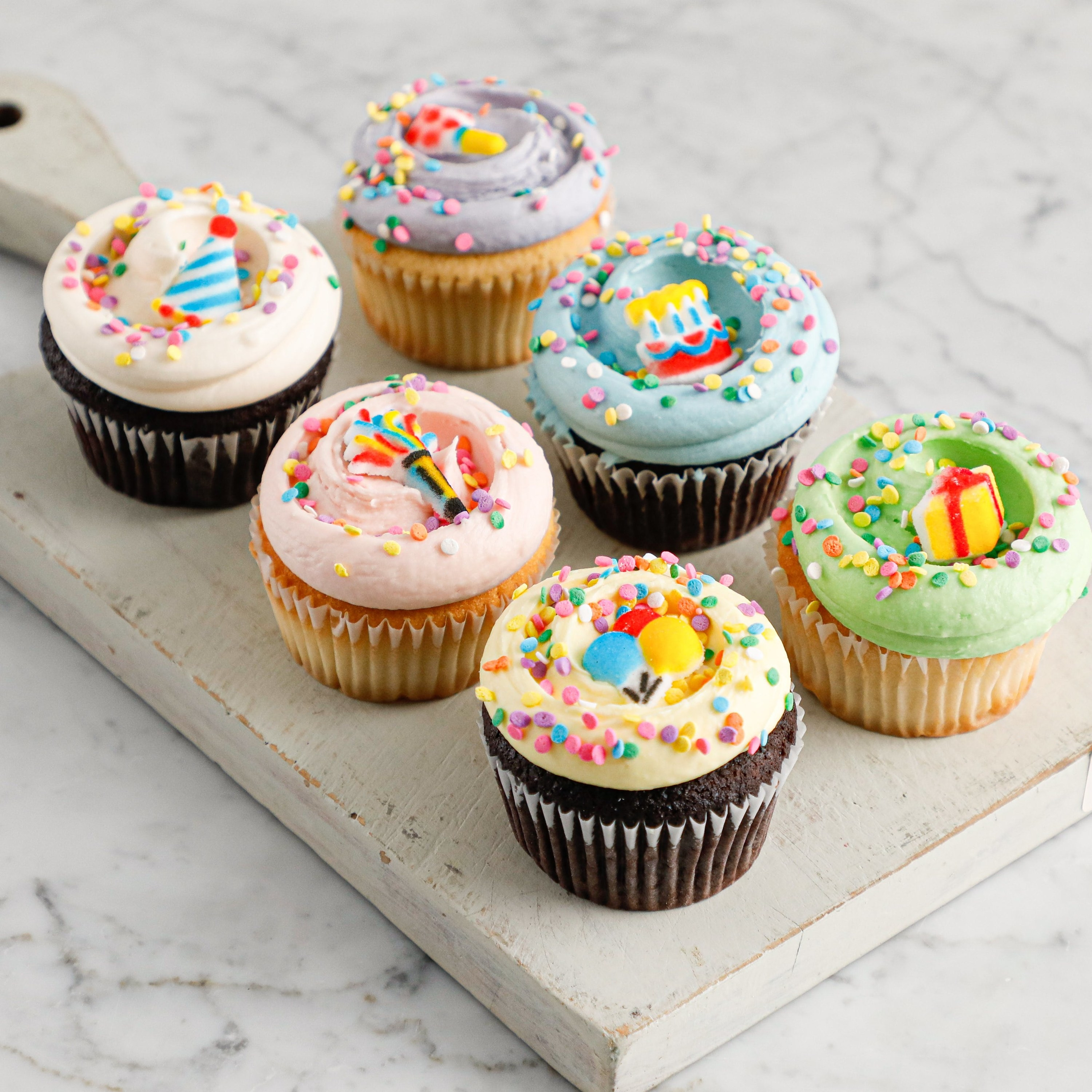 six vanilla and chocolate cupcakes with frosting and sprinkles