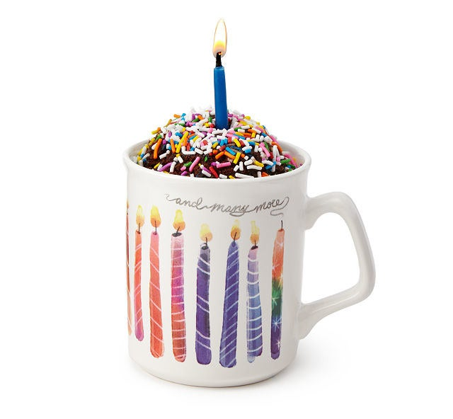 A birthday cake themed mug with cake and a lit candle in it