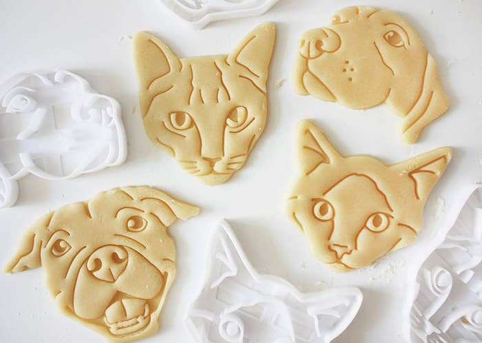 Some pet-shaped cookies next to their cookie cutters