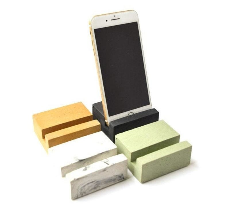 Four small square blocks (in orange, grey marbled effect, green, and black) with indents for a phone, one of which is holding an iPhone.