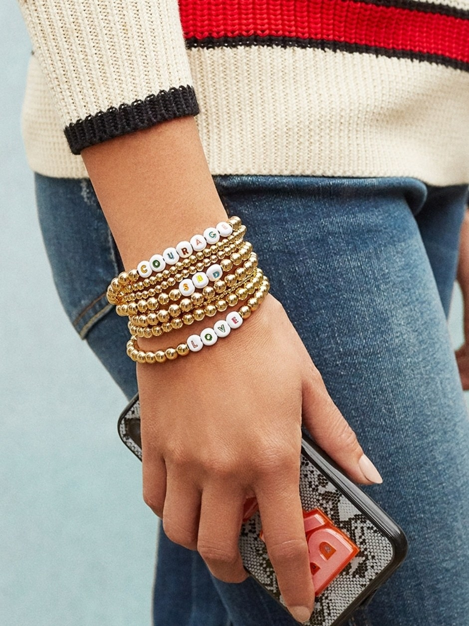 """Model wearing beaded bracelets that spell out """"courage and love"""""""