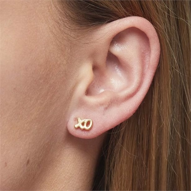 A person's ear with a pair of stud earrings in the shape of an x and o