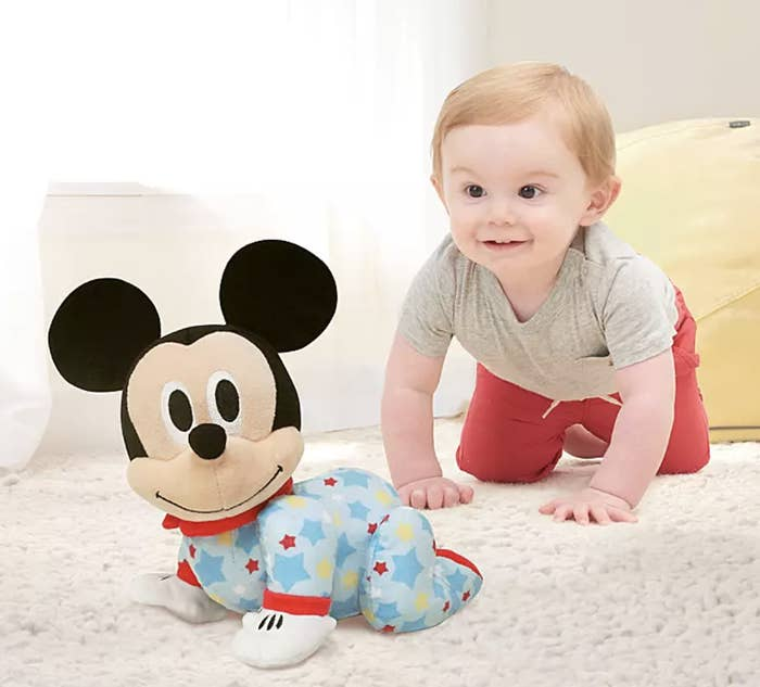 a child crawling alongside a crawling baby version of Mickey