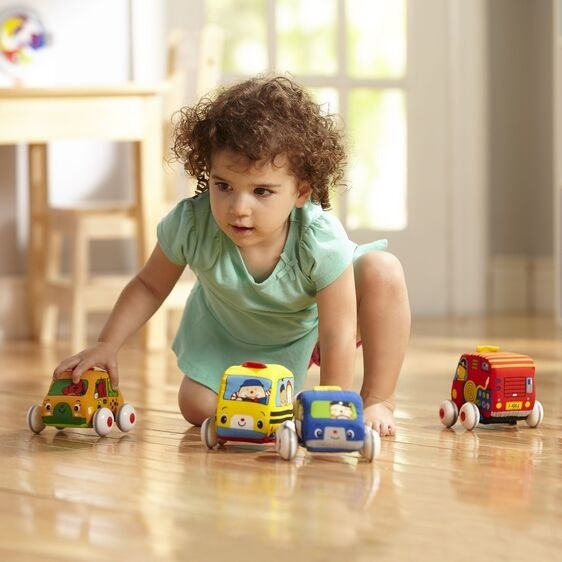 a child playing with the soft cars