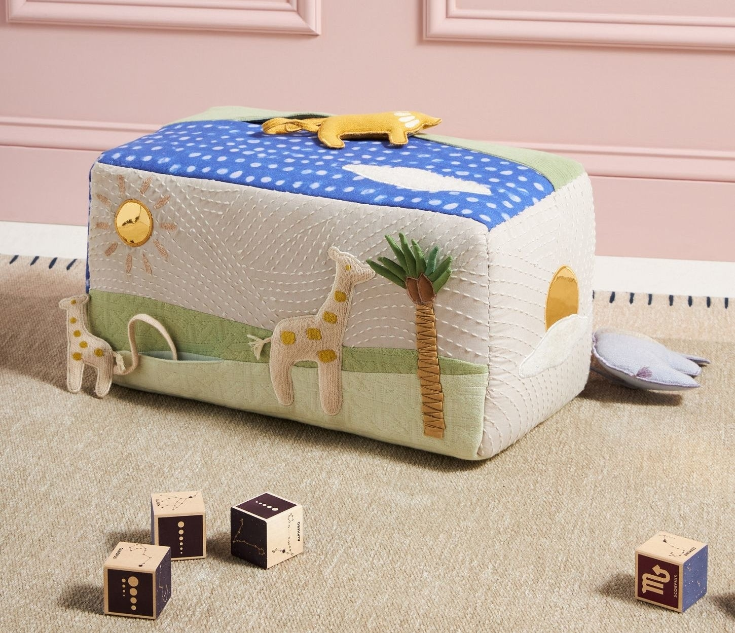a rectangle soft toy with different safari animals on it and a safari scene