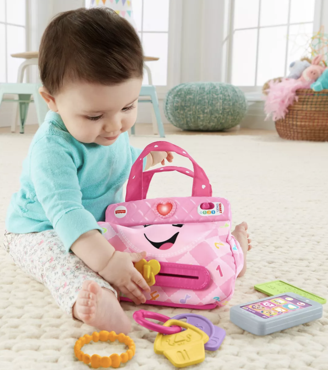 a baby playing with the keys and assorted toys with the purse