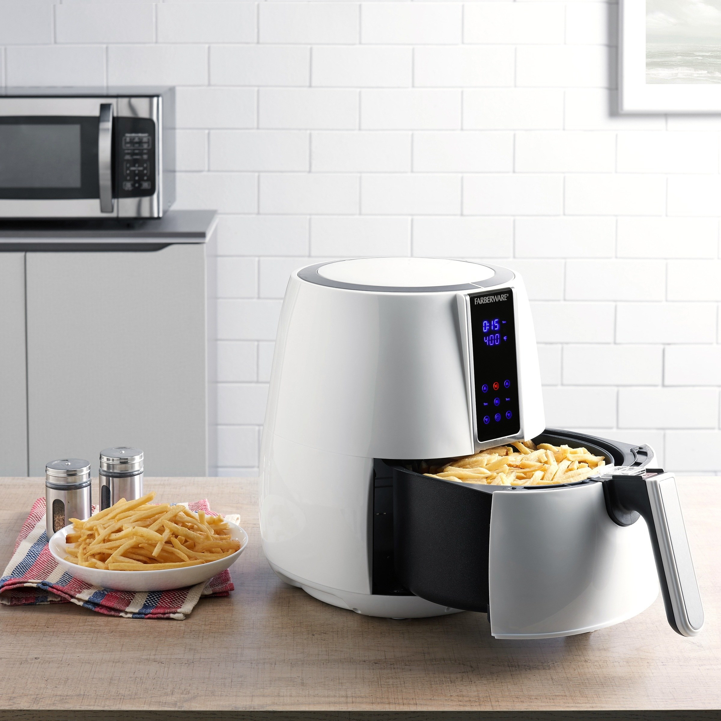 a white air fryer with fries in it