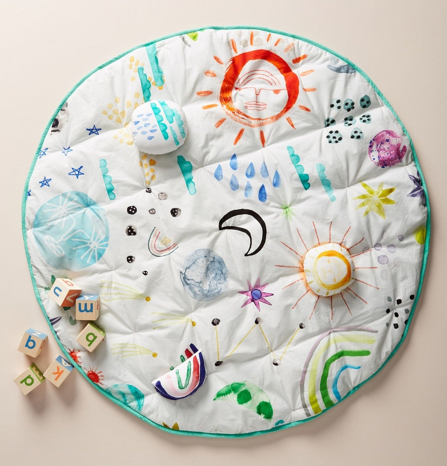 a circle mat covered in different stars and planets in addition to plush play parts
