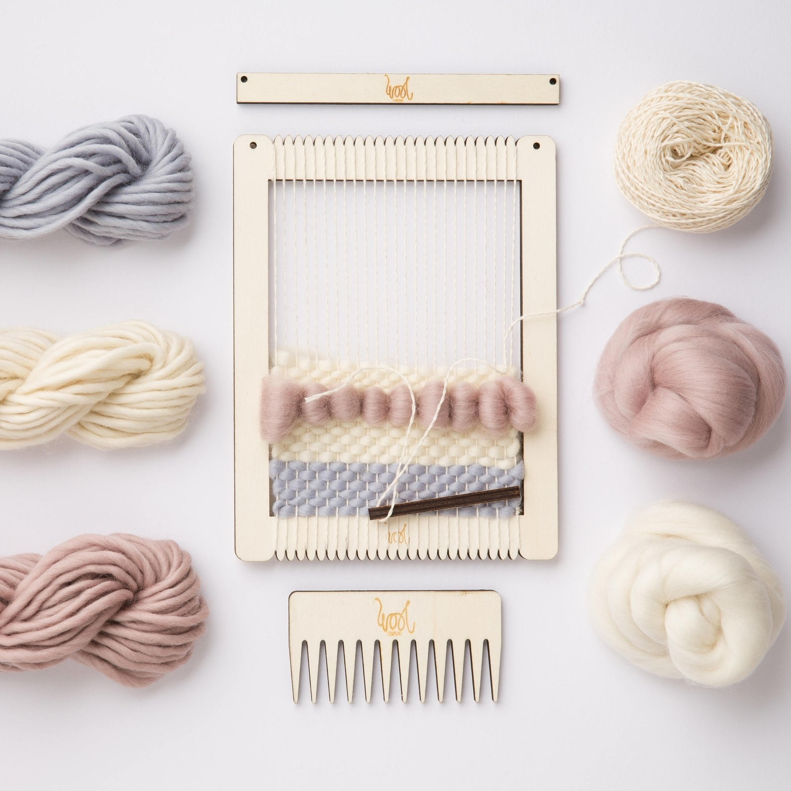A weaving look with half of a project completed on it in dusty pink, blue, and ivory
