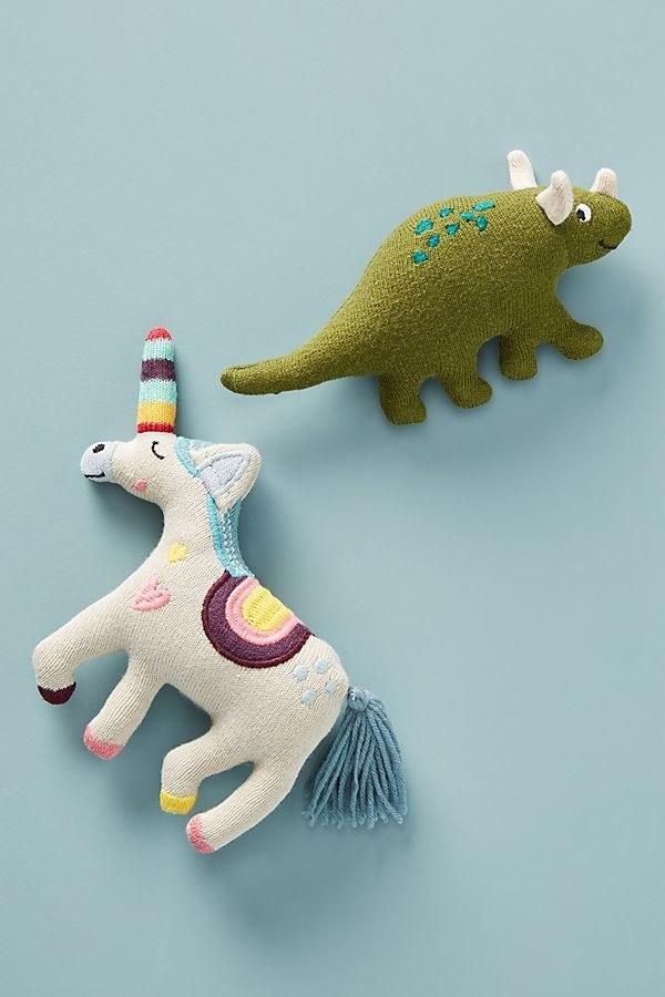a unicorn shaped rattle and a dinosaur shaped rattle