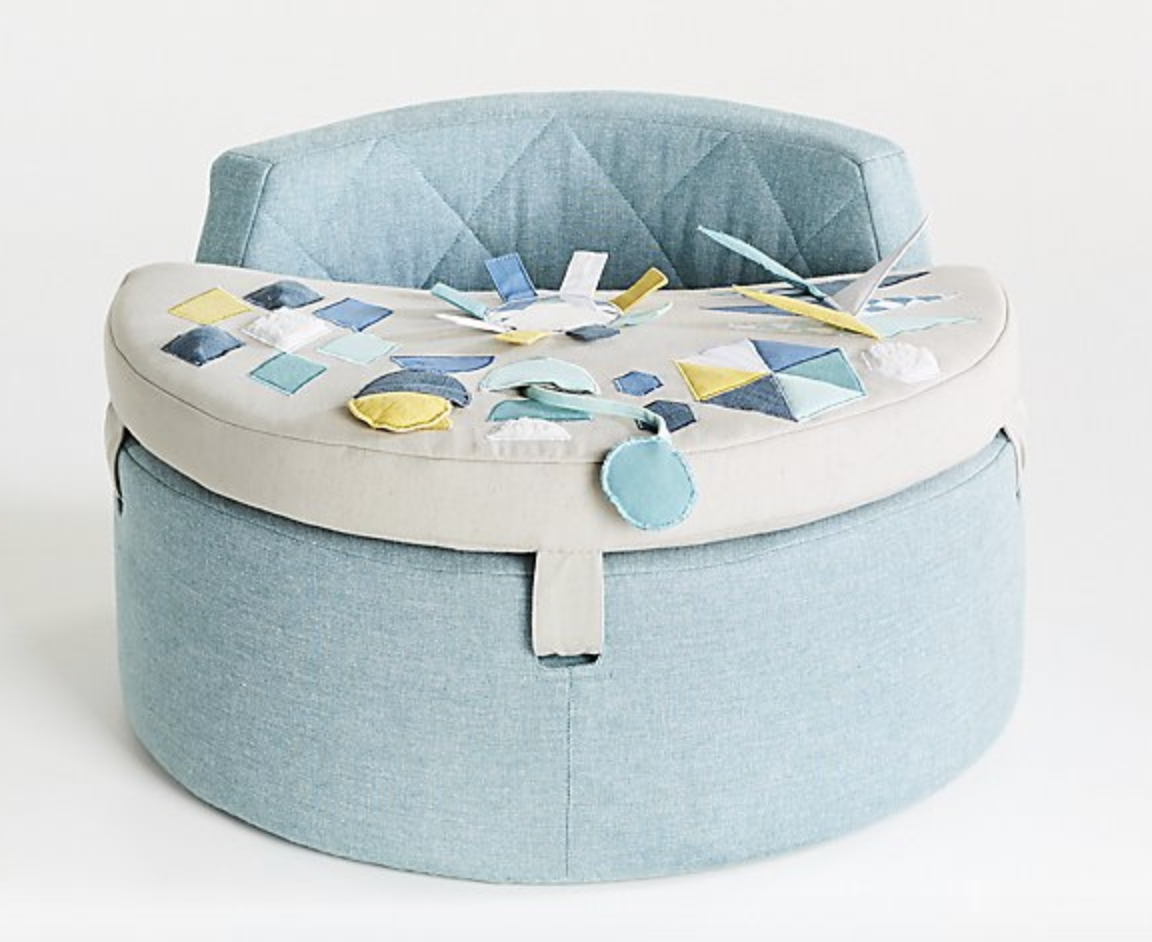a rounded light blue play chair with various flaps and folds on the table for baby to play with