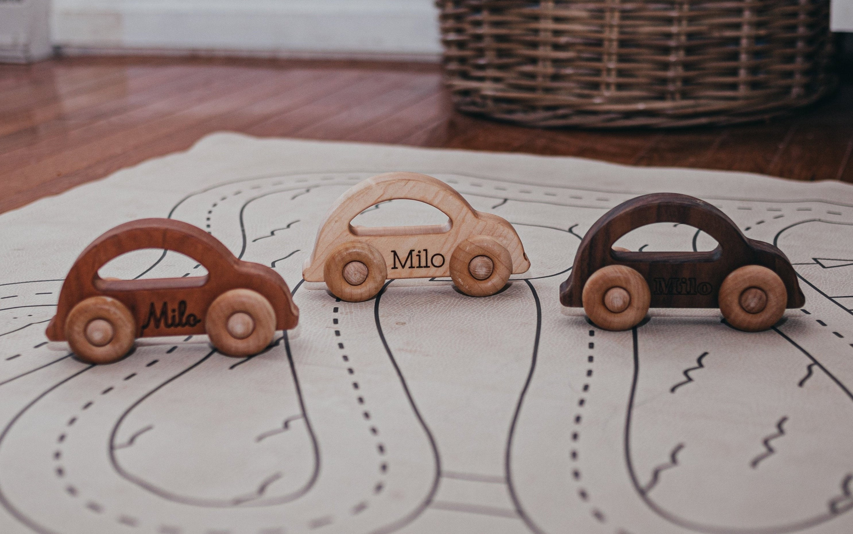 """three cars in different colored woods with the name """"milo"""" written on each one"""