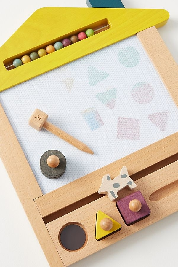 a wooden board with various stamps and a magnetic pencil