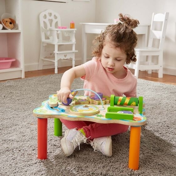 a child sitting at the small table playing with the jungle toys