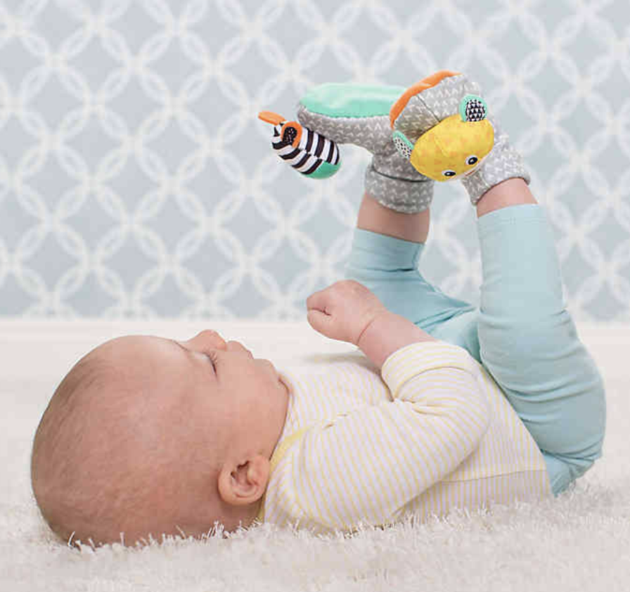 a baby reaching for the rattles on their feet