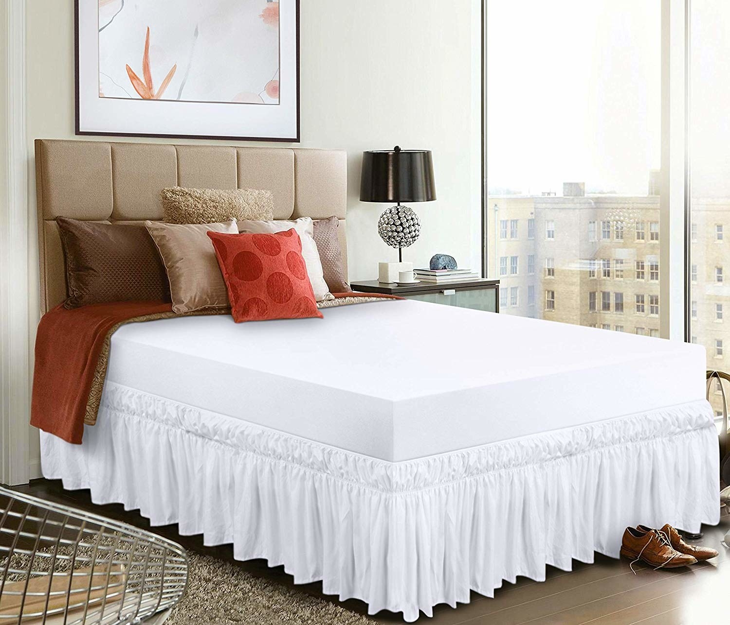 A bed with white sheets and a white dust ruffle all along its edges