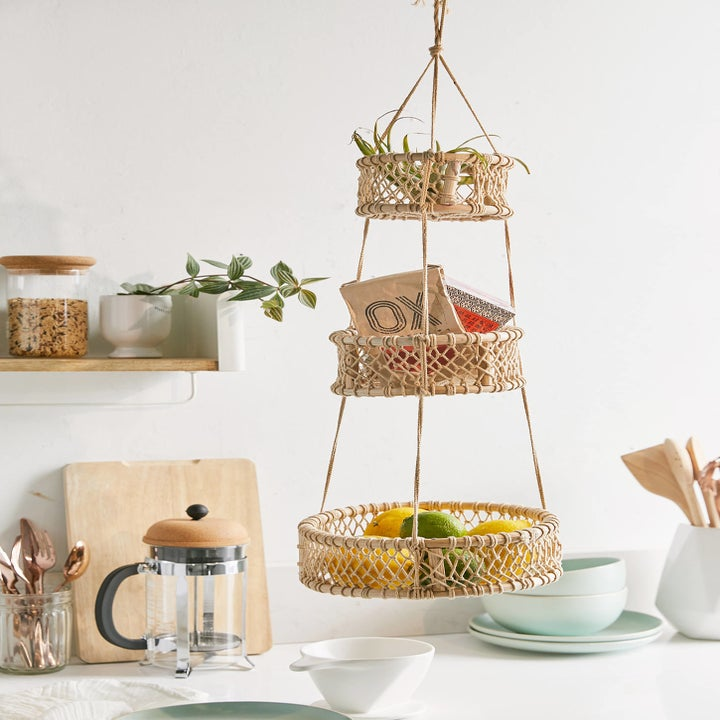 A three tier beige set of hanging baskets with fruit in them