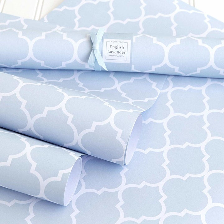A roll of pale blue and white patterned shelf liner