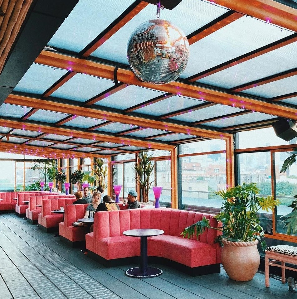 pink booth chairs in a rooftop bar