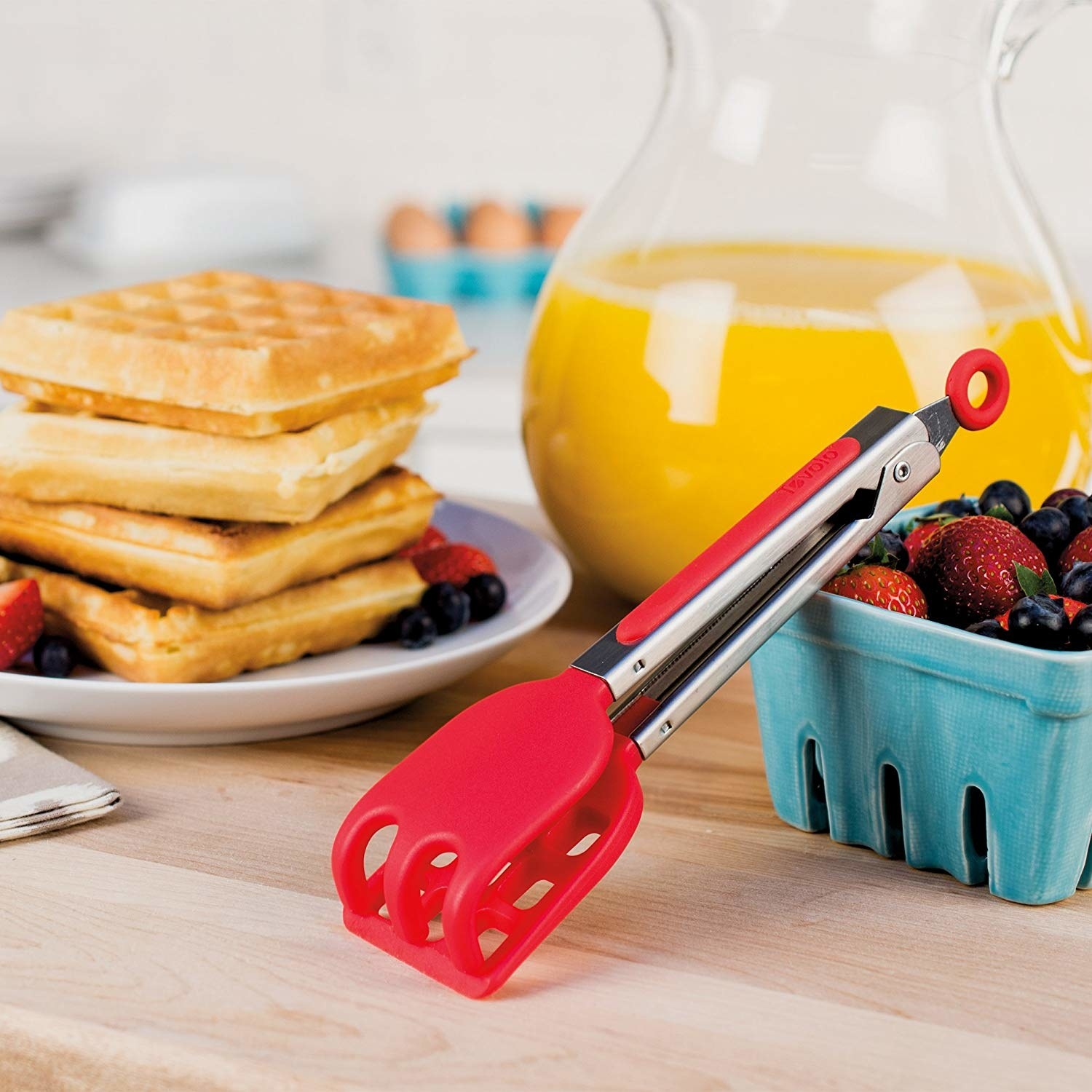A pair of waffle tongs leaning against a carton of berries in front of a stack of waffles