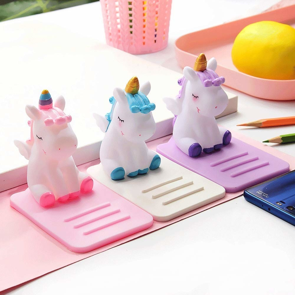 A set of three matching phone holders with ridges that let you lean your phone on little chubby cartoon-y unicorns on the edge of them