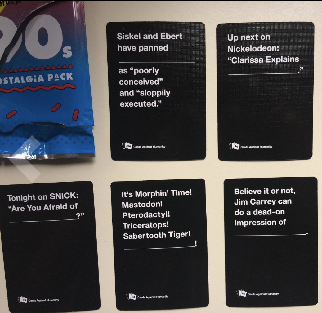 Five black cards with '90s themed prompts and blanks