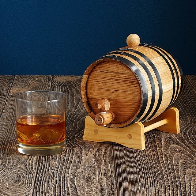 A small whiskey barrel next to a glass of whiskey