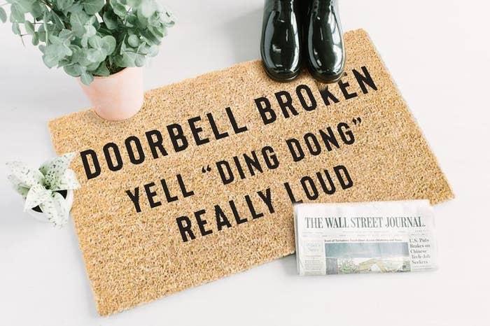 """Doormat reads """"Doorbell Broken Yell 'Ding Dong' Really Loud"""""""