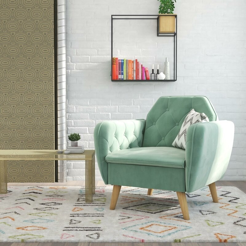 The light green velvet armchair with light wood legs