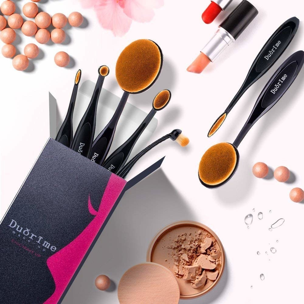 A set of makeup brushes popping out of a small rectangular box Each brush has a oval-shaped head
