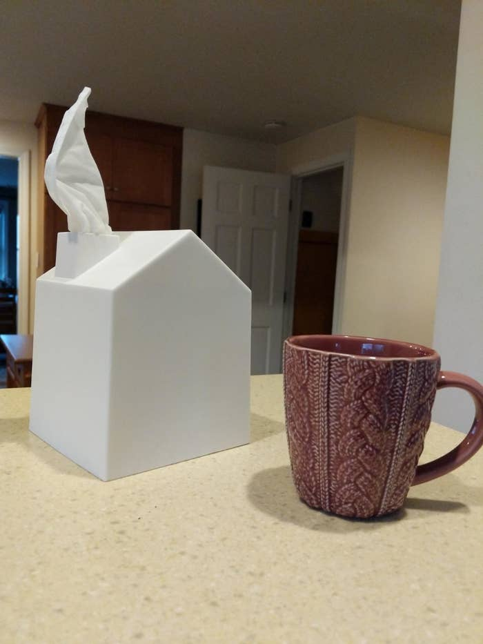 A white tissue box shaped like a house with a chimney that a tissue is coming out of, propped on a table