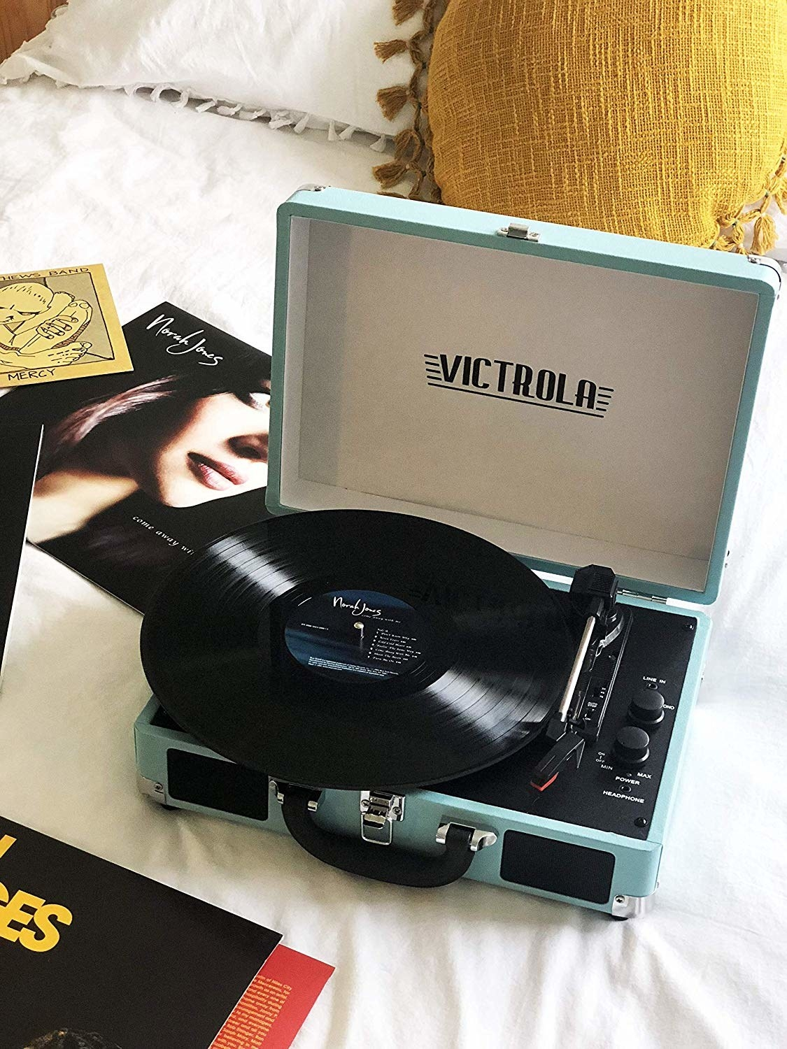 A light blue record player with a norah jones record on it