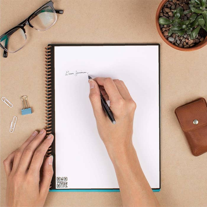 A person writing in the reusable notebook