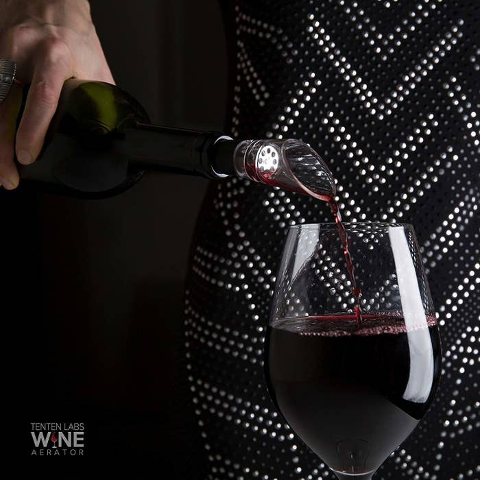 A wine bottle with the glass aerator attached to its top pouring wine into a glass