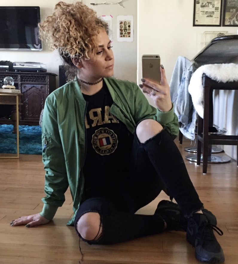 Reviewer wears dark green bomber jacket with distressed black jeans