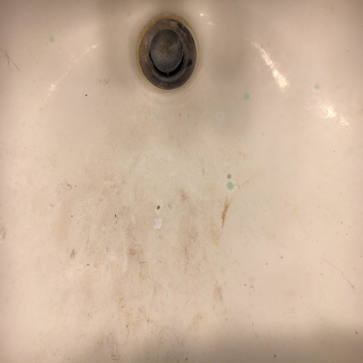 A white porcelain sink with stains on it