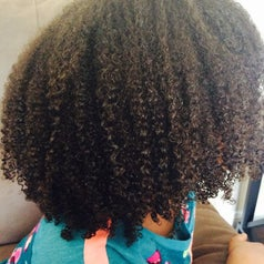 Reviewer with natural hair who used the conditioner to get curl definition and shine