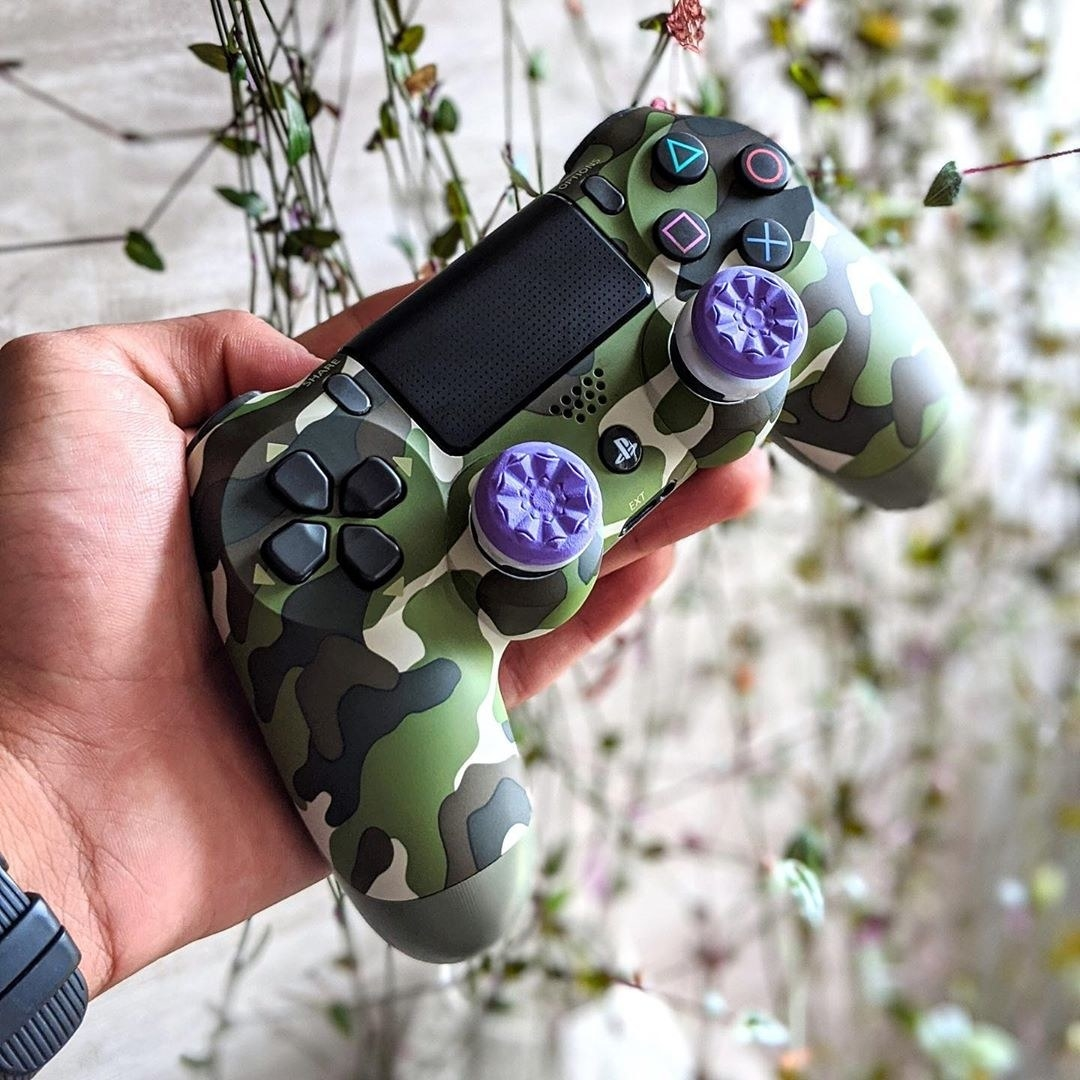 A person holding the camo controller with textured performance grips on it