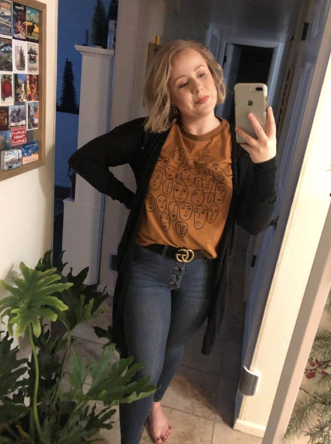 Reviewer wears button up skinny jeans, a black cardigan, and mustard yellow tee with artsy face illustrations